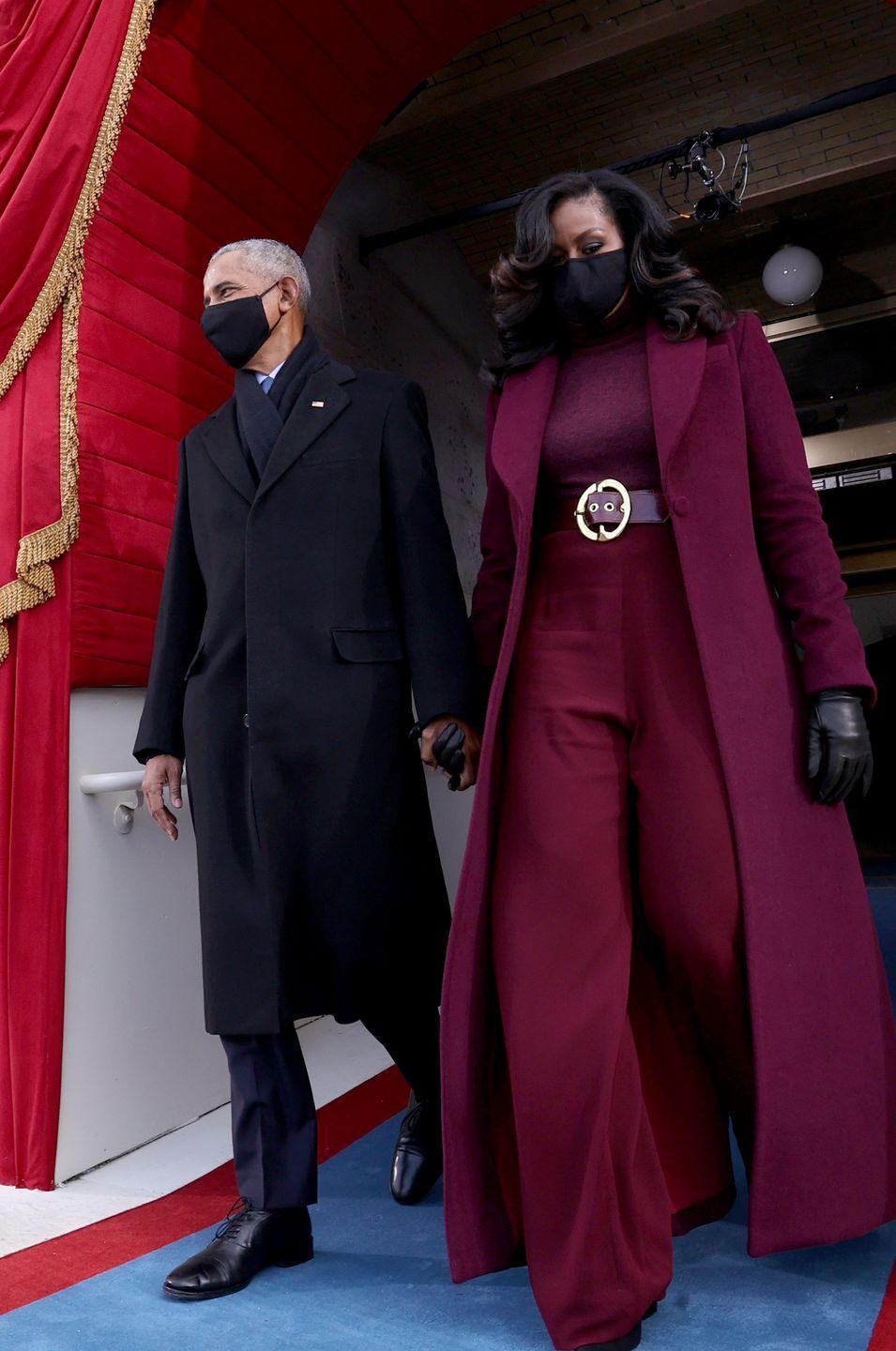 """<p>Here, former First Lady Michelle Obama commands attention and exudes confidence with a head-to-toe burgundy ensemble by <a href=""""https://sergiohudson.com"""" rel=""""nofollow noopener"""" target=""""_blank"""" data-ylk=""""slk:Sergio Hudson"""" class=""""link rapid-noclick-resp"""">Sergio Hudson</a>, a Black designer who hails from South Carolina. The turtleneck, belt, coat, and wide-legged pants make an impactful impression thanks to their monochromatic palette, and she finishes off the statement outfit with <a href=""""https://www.stuartweitzman.com/sale/all-sale/?ogmap=SEM%7CRTN%7CGOOG%7CSTND%7Cc%7CSITEWIDE%7CMain%7CText_Brand_NonCore_ALL%7CGender%7Cstu%20weitzman%7C1497596101%7C63329787523%7CUS&gclid=CjwKCAiAxp-ABhALEiwAXm6IyXBaIDyN9b84xavP7fpdwMUMZEKsXM3PewJpPK3wuUP4hHzsX1HqHhoCjAEQAvD_BwE"""" rel=""""nofollow noopener"""" target=""""_blank"""" data-ylk=""""slk:Stuart Weitzman"""" class=""""link rapid-noclick-resp"""">Stuart Weitzman</a> boots, leather gloves, and a silk mask.</p>"""