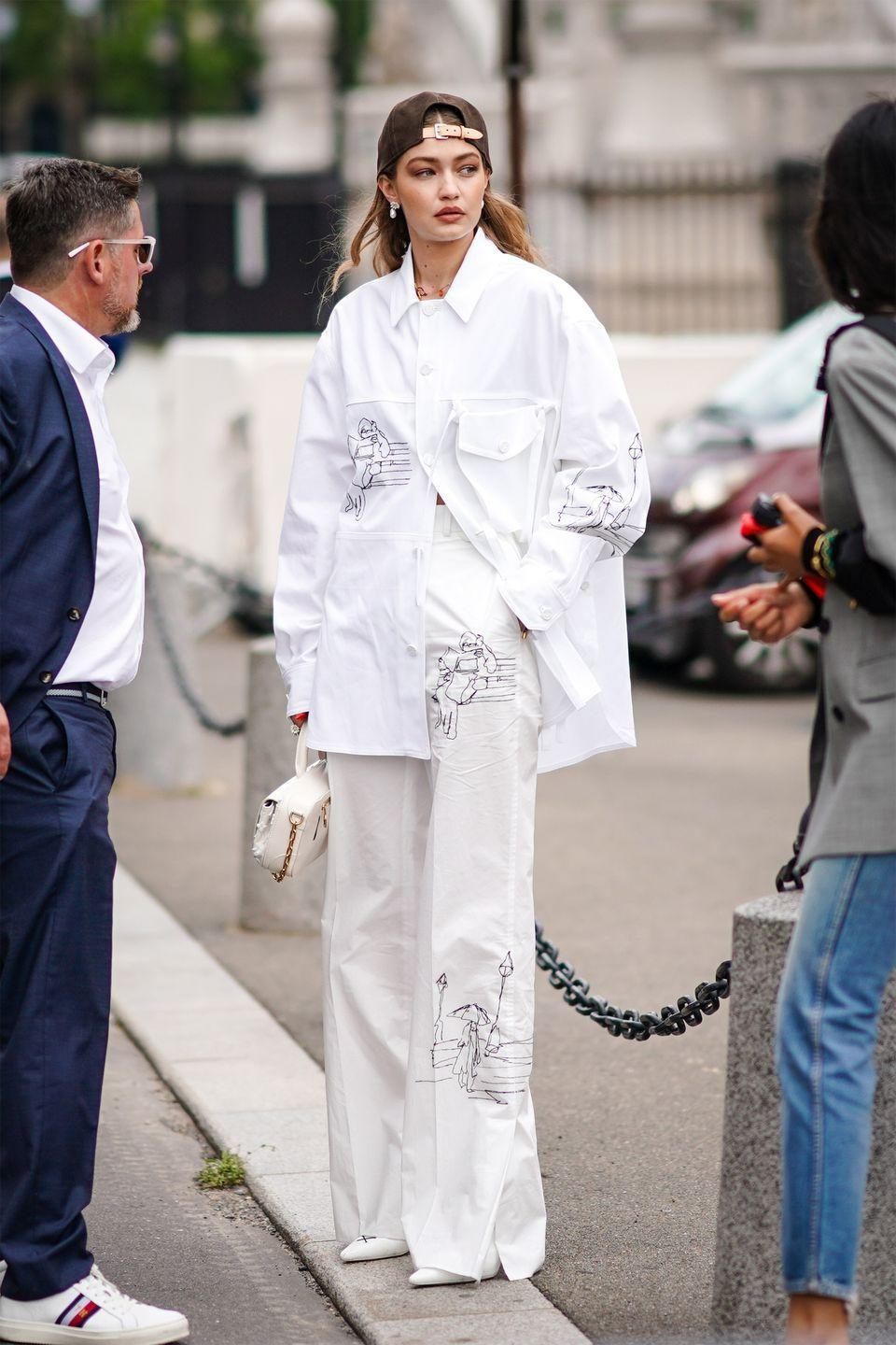 <p>In a brown cap, oversized white button-up, white wide-leg trousers and pointed white shoes.</p>