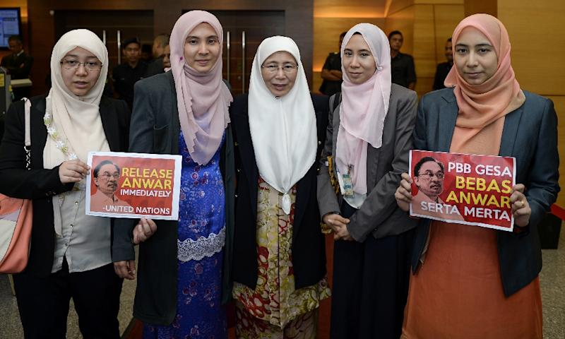 """Malaysian opposition leader Wan Azizah (C) and her daughter Nurul Izzah (2ndL) pose for pictures with placards reading, """"Release Anwar immediately"""" at Parliament House in Kuala Lumpur on November 2, 2015 (AFP Photo/Mohd Rasfan)"""