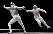 <p>Hungary's Andras Szatmari (L) compete against USA's Daryl Homer in the men's sabre team quarter-final bout during the Tokyo 2020 Olympic Games at the Makuhari Messe Hall in Chiba City, Chiba Prefecture, Japan, on July 28, 2021. (Photo by Mohd RASFAN / AFP)</p>