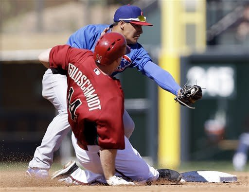 Arizona Diamondbacks' Paul Goldschmidt, foreground, is tagged out by Chicago Cubs shortstop Javier Baez trying to stretch a single into a double during the third inning of an exhibition spring training baseball game on Monday, March 11, 2013 in Scottsdale, Ariz. (AP Photo/Marcio Jose Sanchez)