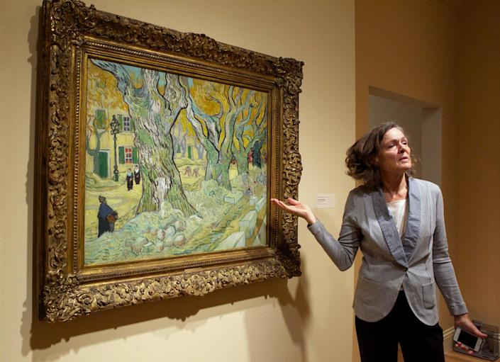 """In this Oct. 8, 2013 photo, the Phillips Collection Director Dorothy Kosinski talks about Vincent van Gogh's """"The Road Menders,"""" at the museum in Washington. In the midst of the shutdown of federally funded museums, the private Phillips Collection is launching the first major exhibition of Vincent van Gogh's artwork in Washington in 15 years. (AP Photo/Molly Riley)"""