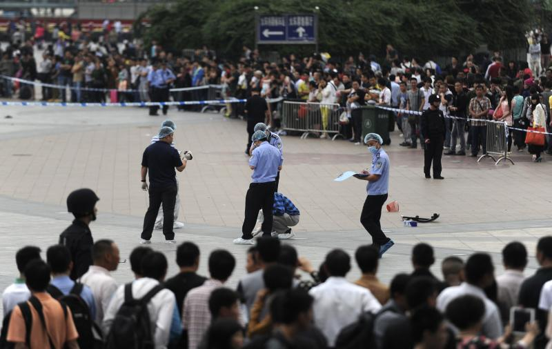 People look on as police officers investigate at the scene after a knife attack at a railway station in Guangzhou