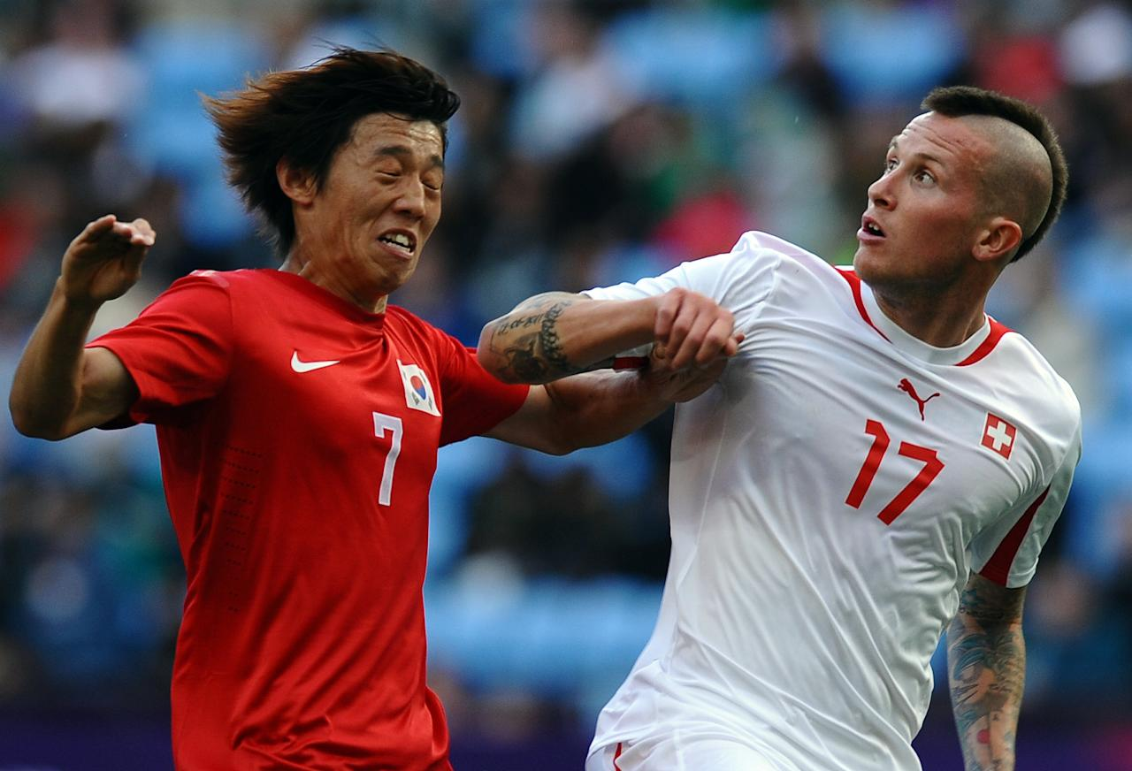Korea's Bokyung Kim (L) challenges Switzerland's Michel Morganella (R) during the London 2012 Olympic men's football match between South Korea and Switzerland at The City of Coventry Stadium in Coventry, central England, on July 29, 2012. AFP PHOTO/PAUL ELLISPAUL ELLIS/AFP/GettyImages