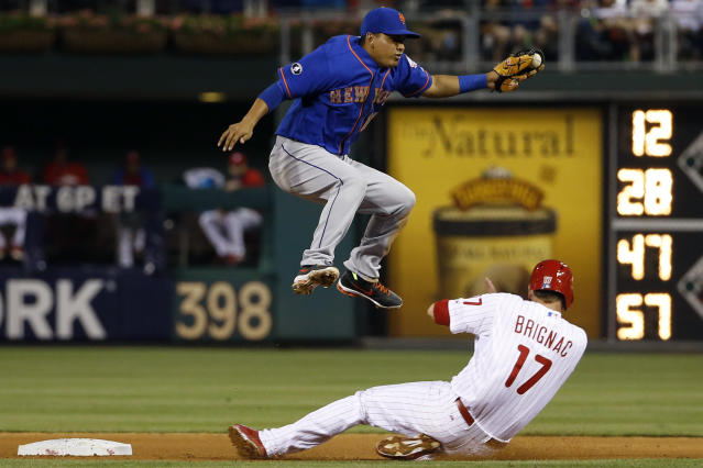 Philadelphia Phillies' Reid Brignac, right, slides into second base under New York Mets shortstop Ruben Tejada to advance on a ball hit by A.J. Burnett during the fourth inning of a baseball game, Friday, May 30, 2014, in Philadelphia. Burnett reached first base and Brignac was safe at second on the throwing error by catcher Travis d'Arnaud. (AP Photo/Matt Slocum)