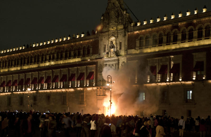 Demonstrators set fire to the door of the main entrance of the Mexican National Palace in Mexico City on November 8, 2014 (AFP Photo/Omar Torres)