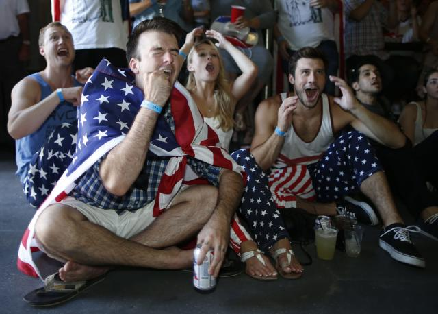 USA soccer fans (L-R) Reid Boutte, 25, McKenzie Anderson, 23, and Andy Shephard, 25, react during the 2014 World Cup Group G soccer match between Portugal and the U.S. at a viewing party in Los Angeles, California June 22, 2014. REUTERS/Lucy Nicholson (UNITED STATES - Tags: SOCCER SPORT WORLD CUP)