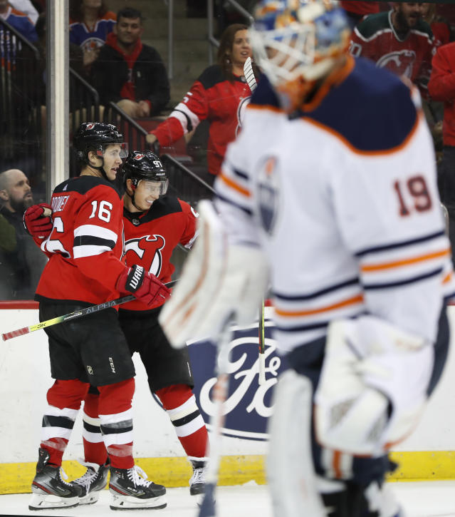 New Jersey Devils center Kevin Rooney (16) and left wing Nikita Gusev (97) celebrate Gusev's goal against Edmonton Oilers goaltender Mikko Koskinen, foreground, during the second period of an NHL hockey game, Thursday, Oct. 10, 2019, in Newark, N.J. (AP Photo/Kathy Willens)