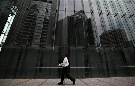 A man walks on a pathway next to a building in Tokyo's business district