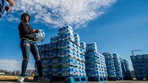 PHOTO: Volunteers load cases of water into vehicles in Flint, Mich., April 22, 2020. (Jake May/The Flint Journal via AP, FILE)