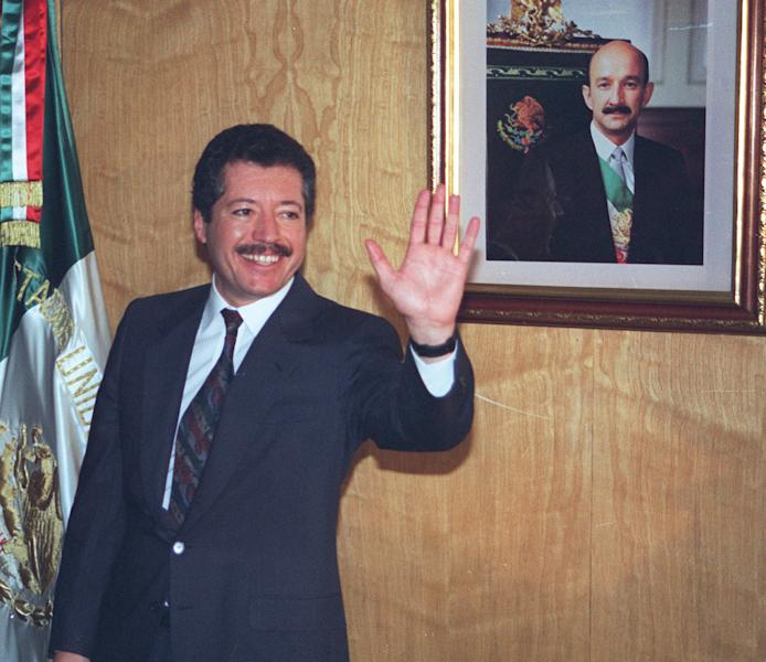 """FILE - In this Nov. 28, 1993 file photo, Luis Donaldo Colosio, then secretary of social development, greets reporters in his Mexico City office, after he was named the ruling Institutional Revolutionary Party's presidential candidate. The film """"Colosio,"""" directed by Mexican Carlos Bolado, portrays the 1994 killing of a candidate who was almost certain to be the next president, casts doubts on the official conclusion that a lone gunman planned and carried out the killing of Colosio, which is often compared to John F. Kennedy's assassination. It is one of several new politically minded films being released just ahead of Mexico's July 1 election that are aimed at reminding Mexicans of the dark side of the Institutional Revolutionary Party, which governed Mexico for 71 years, and which seems set to return to power. (AP photo/Carolos Taboada, File)"""