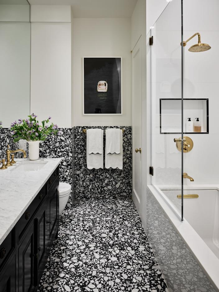 "The guest bathroom features ""Terrazzo Renata"" stone slabs from Ann Sacks, a design inspired by old Italian terrazzo. A Scott Rudin image hangs on the wall."