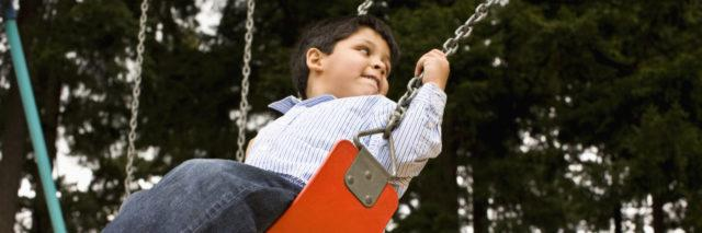 Boy looking over his shoulder while swinging.