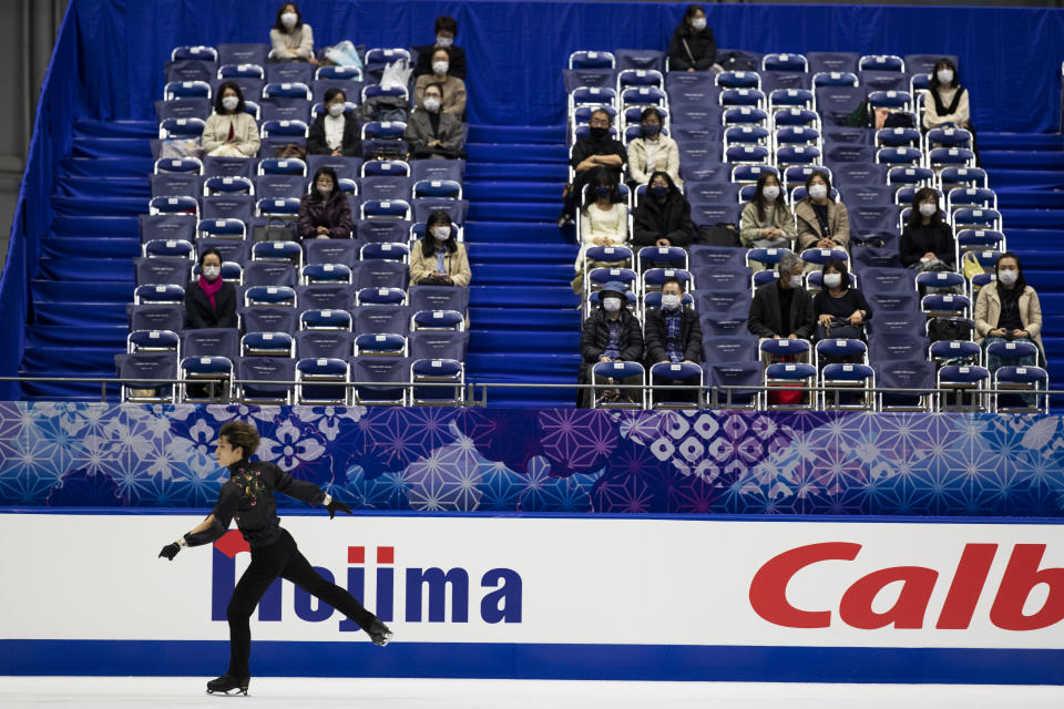 Spectators watch Sena Miyake of Japan warm up during a practice session of an ISU Grand Prix of Figure Skating competition in Kadoma near Osaka, Japan, Friday, Nov. 27, 2020. The event was held with limited spectator attendance Friday. (AP Photo/Hiro Komae)