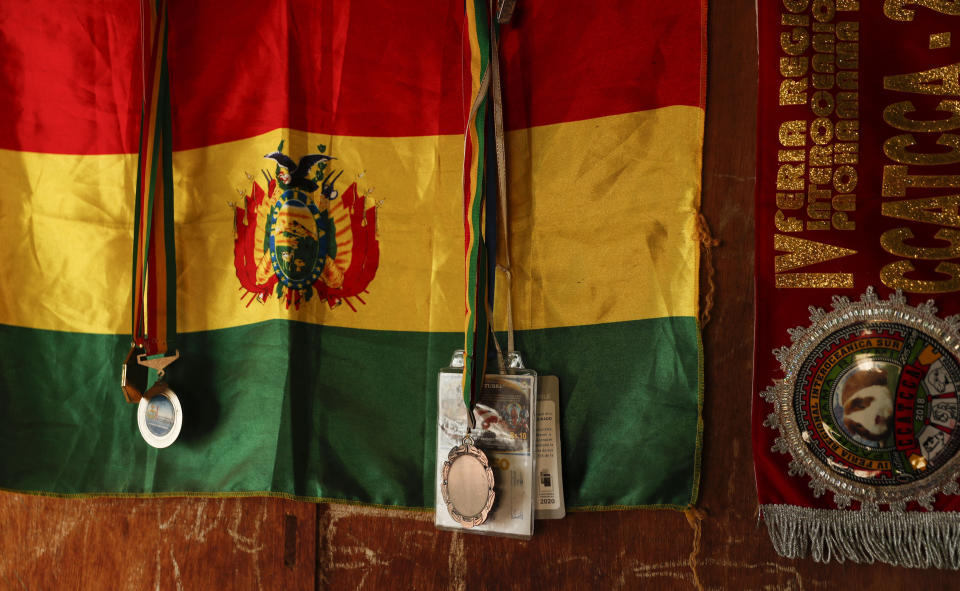 A Bolivian flag hangs behind the boxing medals of Gracce Kelly Flores, a 12-year-old boxer who goes by the nickname Hands of Stone, at her home in Palca, Bolivia, Thursday, June 10, 2021. At age 8, Flores defeated a 10-year-old boy, and with three national boxing medals under her belt, she dreams of reaching the women's boxing world championship. (AP Photo/Juan Karita)