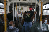 Commuters wearing masks ride a bus during the coronavirus pandemic in the Vermont Square neighborhood of Los Angeles, Thursday, May 21, 2020. While most of California took another step forward to partly reopen in time for Memorial Day weekend, Los Angeles County didn't join the party because the number of coronavirus cases has grown at a pace that leaves it unable to meet even the new, relaxed state standards for allowing additional businesses and recreational activities. (AP Photo/Jae C. Hong)
