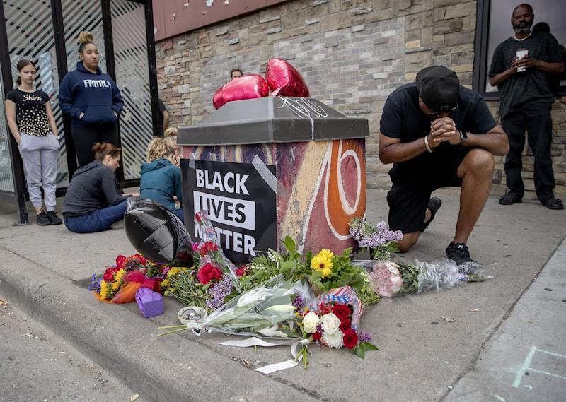 People gather and pray around a makeshift memorial near the site where the man died. Source: AP