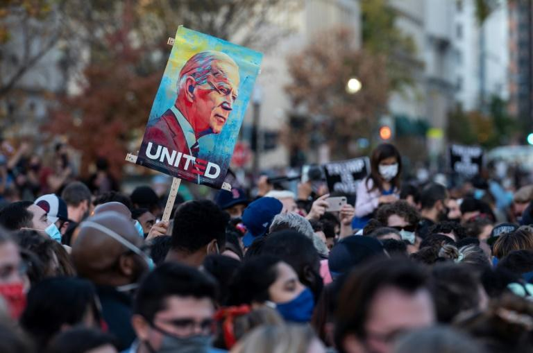 People celebrate Joe Biden's victory in the election at Black Lives Matter Plaza across from the White House in Washington, DC at the weekend