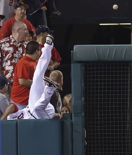 Los Angeles Angels left fielder Vernon Wells falls over the wall as he tries to catch a two-run home run by Texas Rangers' Ian Kinsler in the third inning of a baseball game in Anaheim, Calif., Tuesday, Sept. 18, 2012. (AP Photo/Jae C. Hong)