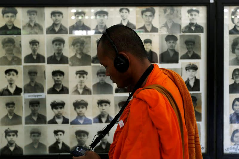 A Buddhist monk looks at pictures of victims of the Khmer Rouge regime at Tuol Sleng Genocide Museum in Phnom Penh