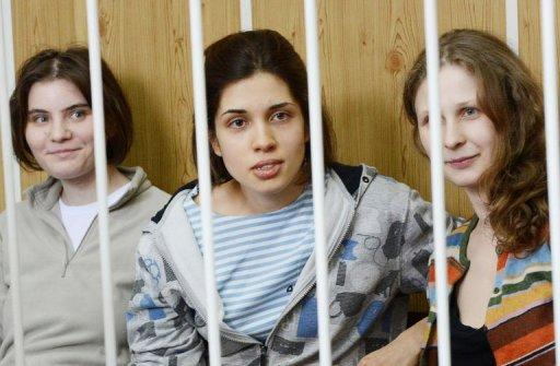 """Members of the all-girl punk band """"Pussy Riot"""" Nadezhda Tolokonnikova (C), Maria Alyokhina (R) and Yekaterina Samutsevich (L), sitting behind bars during a court hearing in Moscow. US pop icon Madonna said Tuesday she prayed for the freedom of all-girl band Pussy Riot after prosecutors sought three years' prison for its members for performing an anti-Putin """"punk prayer"""" in a church"""