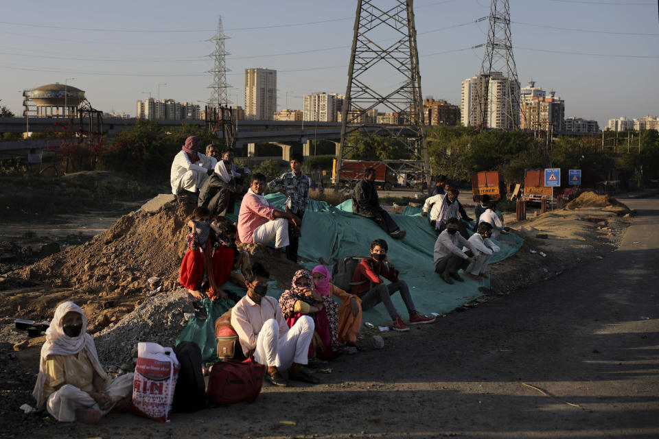 A group of Indian migrant workers rest as they wait for transportation to their village following a lockdown amid concern over spread of coronavirus in New Delhi, India, Saturday, March 28, 2020. Authorities sent a fleet of buses to the outskirts of India's capital on Saturday to meet an exodus of migrant workers desperately trying to reach their home villages during the world's largest coronavirus lockdown. Thousands of people, mostly young male day laborers but also families, fled their New Delhi homes after Prime Minister Narendra Modi announced a 21-day lockdown that began on Wednesday and effectively put millions of Indians who live off daily earnings out of work. (AP Photo/Altaf Qadri)