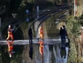 Railway workers are seen crossing the tracks after the river Thames flooded the railway in the village of Datchet, southern England February 10, 2014. REUTERS/Eddie Keogh