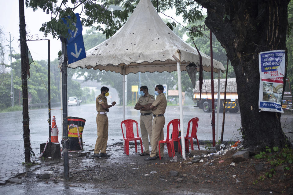 Policemen enforcing a lockdown to curb the spread of coronavirus stand beneath a rain shelter in Kochi, Kerala state, India, Sunday, May 16, 2021. A severe cyclone is roaring in the Arabian Sea off southwestern India with winds of up to 140 kilometers per hour (87 miles per hour), already causing heavy rains and flooding that have killed at least four people, officials said Sunday. (AP Photo/R S Iyer)