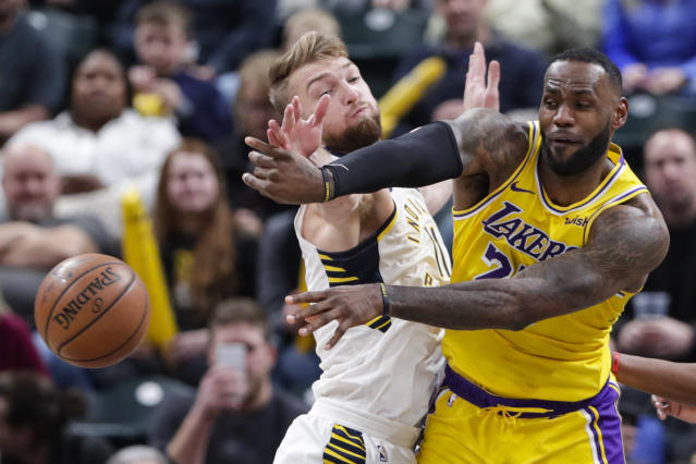 Los Angeles Lakers forward LeBron James (23) makes a pass in front of Indiana Pacers forward Domantas Sabonis (11) during the second half of an NBA basketball game in Indianapolis, Tuesday, Dec. 17, 2019. The Pacers defeated the Lakers 105-102. (AP Photo/Michael Conroy)