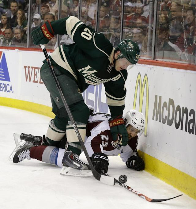 Minnesota Wild defenseman Ryan Suter (20) and Colorado Avalanche center Maxime Talbot (25) battle for the puck during the second period of Game 4 of an NHL hockey first-round playoff series in St. Paul, Minn., Thursday, April 24, 2014. (AP Photo/Ann Heisenfelt)
