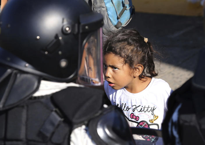 A migrant girl looks at Mexican National Guardsmen at the border crossing between Guatemala and Mexico in Tecun Uman, Guatemala, Saturday, Jan. 18, 2020. More than a thousand Central American migrants surged onto the bridge spanning the Suchiate River, that marks the border between both countries, as Mexican security forces attempted to impede their journey north. (AP Photo/Marco Ugarte)