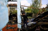 Locals inspect the house hit by a rocket during the fighting over the breakaway region of Nagorno-Karabakh, in the village of Baharli
