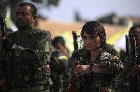 A fighter of Syrian Democratic Forces (SDF) holds her weapon as they announce the destruction of Islamic State's control of land in eastern Syria