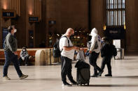Travelers make their way through the 30th Street Station ahead of the Thanksgiving holiday, Friday, Nov. 20, 2020, in Philadelphia. With the coronavirus surging out of control, the nation's top public health agency pleaded with Americans not to travel for Thanksgiving and not to spend the holiday with people from outside their household. (AP Photo/Matt Slocum)