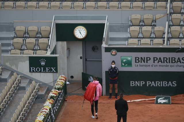 Victoria Azarenka walks out of a near-empty Suzanne Lenglen Court after her French Open first round match against Danka Kovinic is suspended because of the weather
