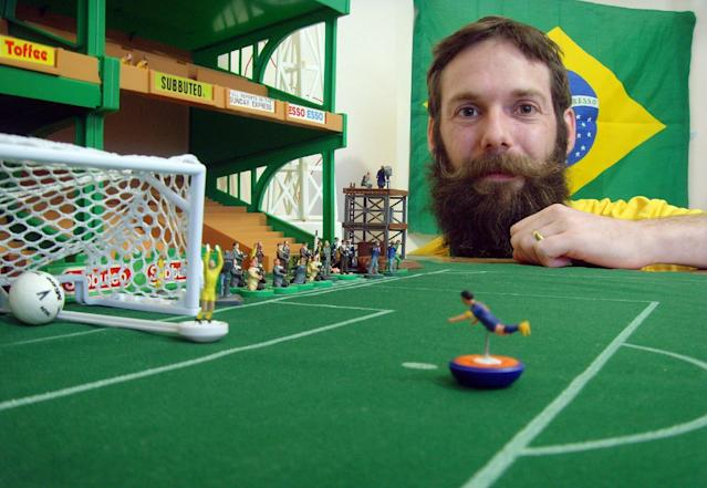 British artist Terry Lee, who lives in Brazil, poses with some of his football figurines in his studio outside Rio de Janeiro on June 19, 2014 (AFP Photo/)
