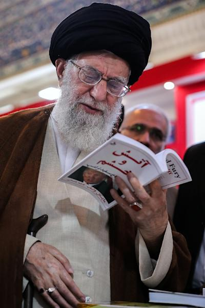 "A handout picture provided by the office of Iran's Supreme Leader Ayatollah Ali Khamenei on May 11, 2018 shows him reading a translation of ""Fire and Fury"" by Michael Wolff during his tour of the book fair in the capital Tehran. (AFP Photo/Handout)"