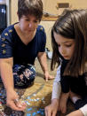 In this photo provided by Christina Neu, Christina Neu works on a puzzle with her six-year-old daughter Charissa Wednesday, June 9, 2021, in Wichita, Kan. Neu didn't enroll Charissa in kindergarten last fall even though she would have been one of the older kids in her class because of concerns about the pandemic. (Christina Neu via AP)