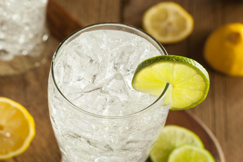 A glass of sparkling water with slices of lemons and limes.