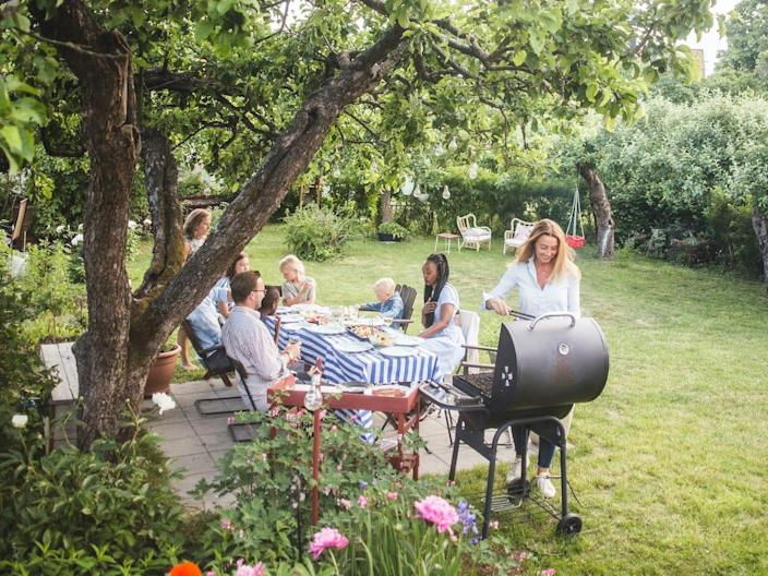 People sit at a table in a backyard while someone grills next to them.