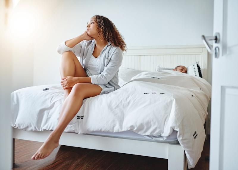 Shot of a irritated young woman sitting on bed while her husband sleeps in the background