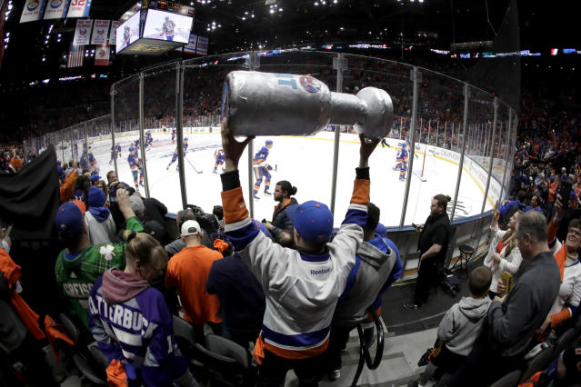 FILE - In this April 10, 2019, file photo, New York Islanders players take the ice as a man holds a makeshift Stanley Cup prior to Game 1 of an NHL hockey first-round playoff series against the Pittsburgh Penguins in Uniondale, N.Y. (AP Photo/Julio Cortez, FIle)