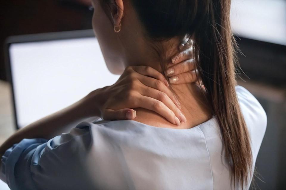 Tired woman massaging rubbing stiff sore neck tensed muscles fatigued from computer work in incorrect posture