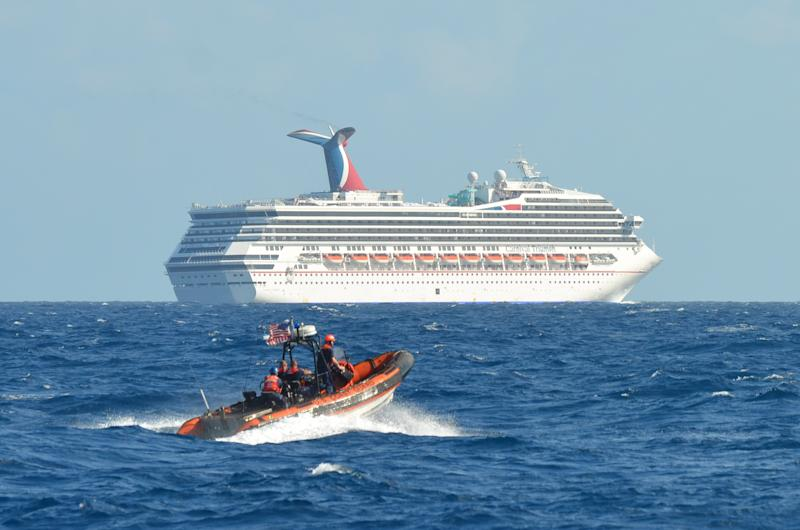 In this image released by the U.S. Coast Guard on Feb. 11, 2013, a small boat belonging to the Coast Guard Cutter Vigorous patrols near the cruise ship Carnival Triumph in the Gulf of Mexico, Feb. 11, 2013. The Carnival Triumph has been floating aimlessly about 150 miles off the Yucatan Peninsula since a fire erupted in the aft engine room early Sunday, knocking out the ship's propulsion system. No one was injured and the fire was extinguished. (AP Photo/U.S. Coast Guard- Lt. Cmdr. Paul McConnell)