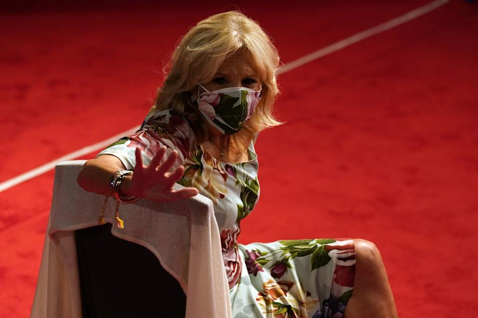 Jill Biden, wearing a floral mask that matches her dress, sits in a chair in the debate hall