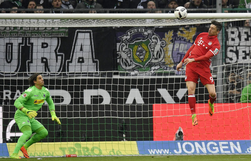 Bayern's Robert Lewandowski jumps for the ball beside Moenchengladbach goalkeeper Yann Sommer during the German Bundesliga soccer match between Borussia Moenchengladbach and Bayern Munich in Moenchengladbach, Germany, Sunday, March 19, 2017. (AP Photo/Martin Meissner)