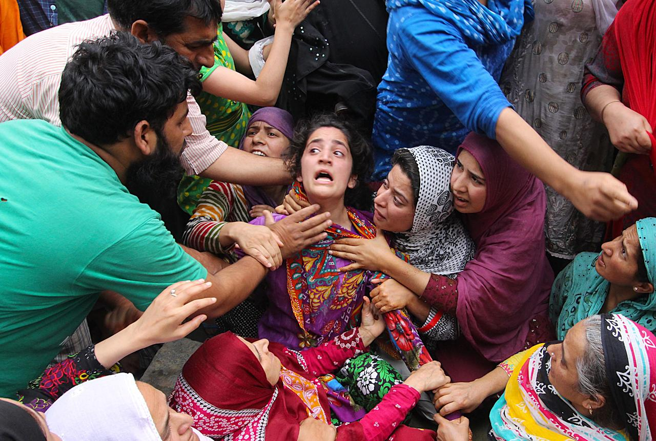 <p>Mehvish (C), sister of Irfan Ahmad, who was killed by a teargas canister fired by Indian security forces, mourns during a protest in Srinagars Fateh Kadal, Kashmir, India on August 22, 2016. (Faisal Khan/Anadolu Agency/Getty Images) </p>