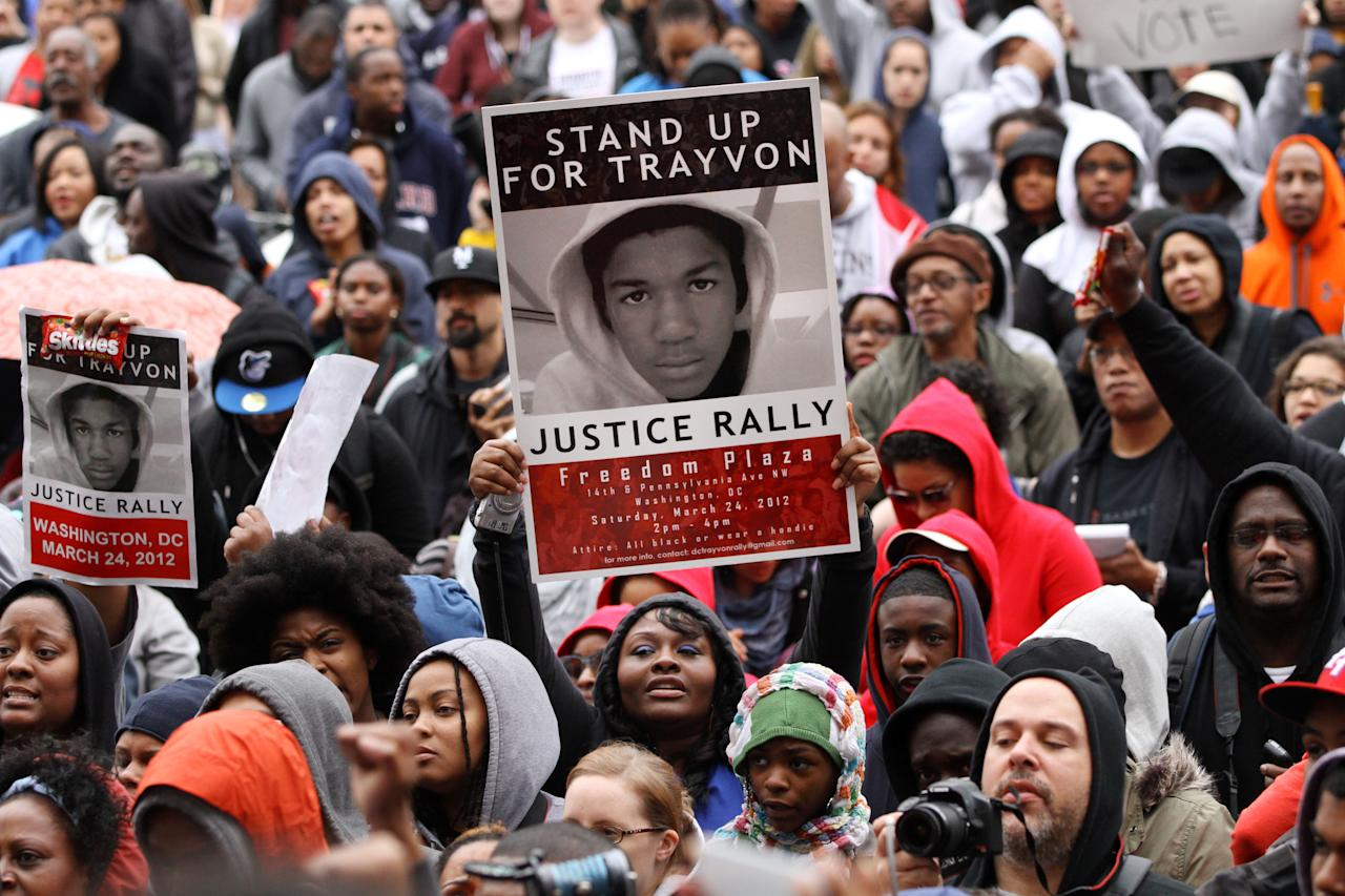 People hold up signs and bags of Skittles candy during a rally in support of Trayvon Martin at Freedom Plaza in Washington, on Saturday, March 24, 2012. Many people in attendance brought candy, cans of ice tea, and wore hooded sweatshirts, or hoodies, in support of the slain teenager. (AP Photo/Jacquelyn Martin)
