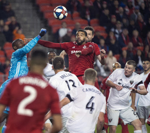 D.C. United goalkeeper Bill Hamid, left, knocks the ball away from Toronto FC forward Jordan Hamilton, center, during the second half of an MLS soccer game, Wednesday, May 15, 2019 in Toronto. (Nathan Denette/The Canadian Press via AP)