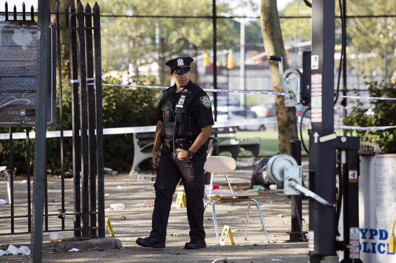 FILE - In this July 28, 2019 file photo, a police officer walks by yellow evidence markers at a playground after a shooting in the Brownsville neighborhood in the Brooklyn borough of New York. New York City police have made an arrest in the community festival shooting that left one person dead and 11 wounded this summer. Police said Wednesday, Oct. 16, that 20-year-old Kyle Williams, of Brooklyn, was arrested on murder, criminal possession of a weapon, reckless endangerment and attempted murder charges. (AP Photo/Mark Lennihan, File)